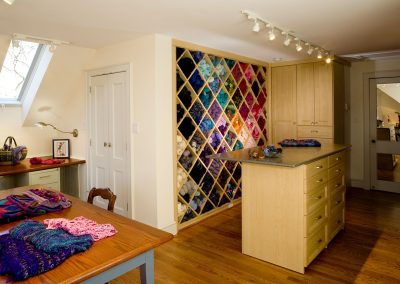 A craft studio with a wall for fabrics inset