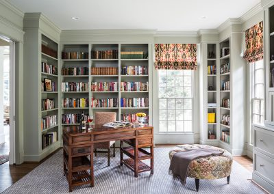 A library and office with desk, book shelves