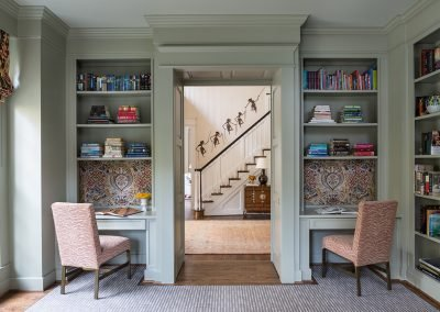 An office with two sitting spaces, book shelves and a door to the foyer