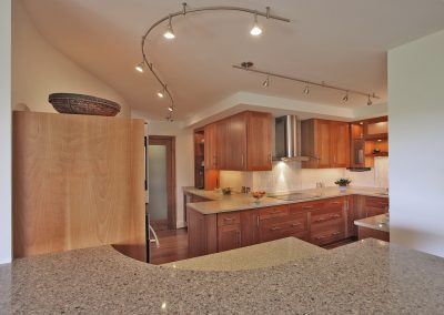 A kitchen remodeled with wood cabinets and stone countertops