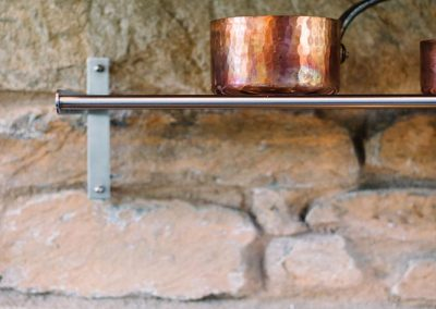 A shelf in a rustic kitchen with bronze cookware