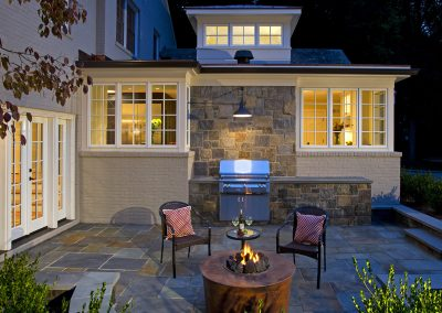 A patio with a firepit and outdoor grill