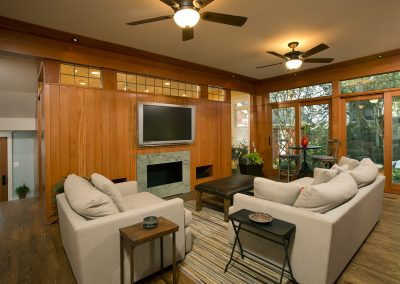 A living room with large doors to the patio and a fireplace
