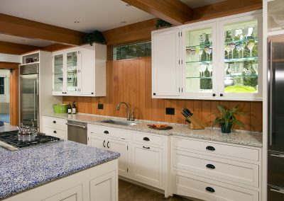 A wood paneled kitchen with white cabinets and stone countertops