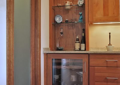 A remodeled kitchen with wine fridge and wood cabinets