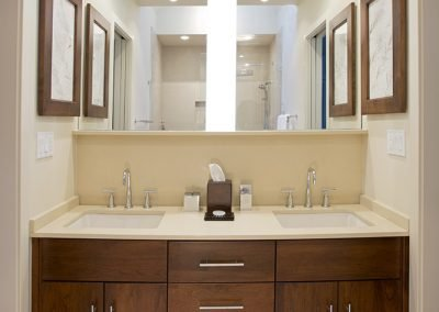 A bathroom with large mirror, wood cabinets