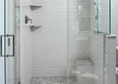 A shower with a bench and built in shelves